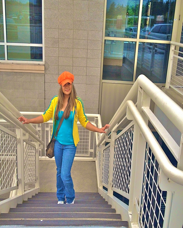 MidoriLei wears an orange hat, yellow and teal sporty cardigan with two stripes, a striped teal tube top, an olive messenger bag, jeans, and gray and white sneakers