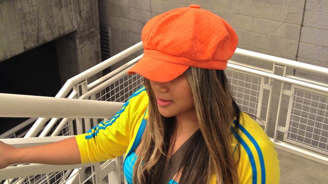 MidoriLei wears an orange hat, yellow and teal sporty cardigan with two stripes, a striped teal tube top, an olive messenger bag