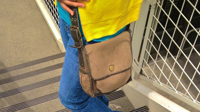 MidoriLei wears a yellow and teal sporty cardigan with two stripes, a striped teal tube top, an olive messenger bag, jeans
