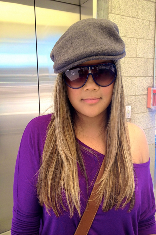 MidoriLei wears a gray felt hat, sunglasses, a purple off the shoulder shirt, a brown leather messenger bag