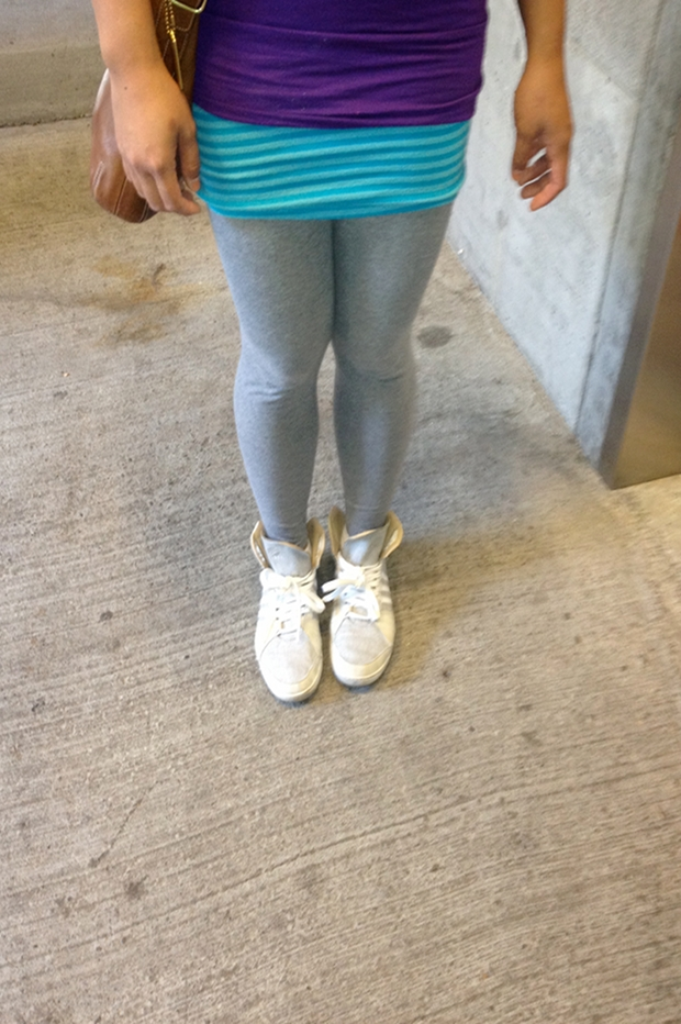 MidoriLei wears a purple shirt, a teal mini skirt, a brown leather messenger bag, gray leggings, and gray and white sneakers