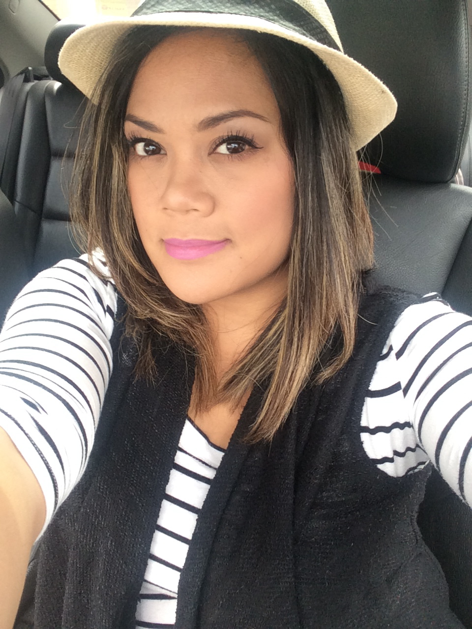 Midorilei wears a black and white shirt, black vest, a fedora, and purple lipstick