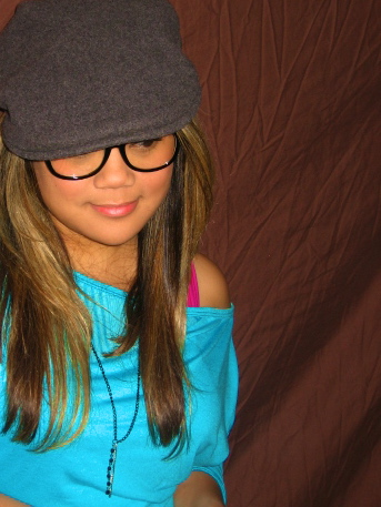 MidoriLei wears black nerdy glasses, a gray felt hat, teal off the shoulder shirt, and fuchsia bra