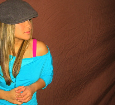 MidoriLei wears a teal off the shoulder 3/4th sleeve shirt, fuchsia bra, and gray felt hat