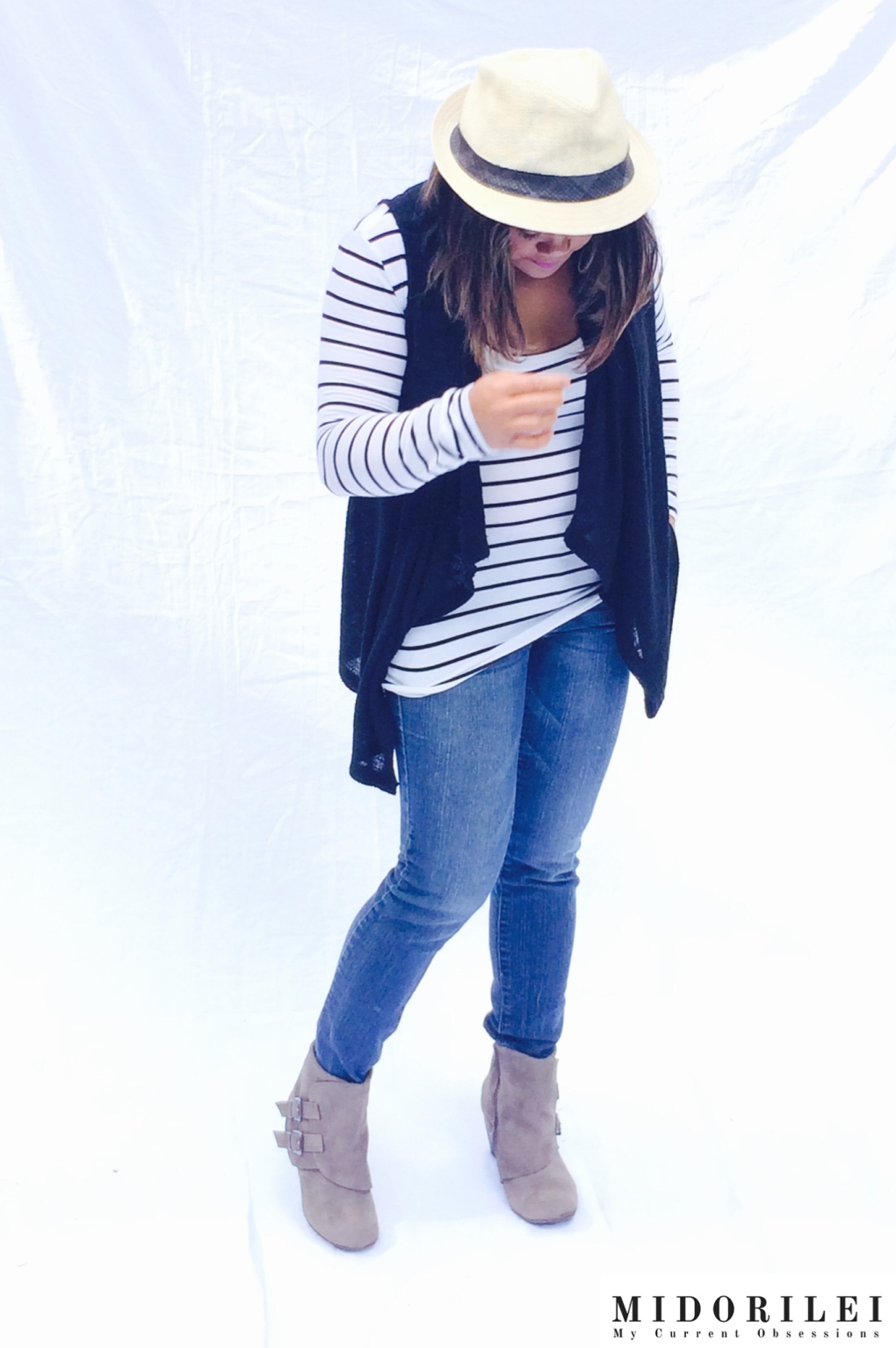 Midorilei wears taupe ankle booties, skinny jeans, a black and white striped shirt, a black vest, and a fedora