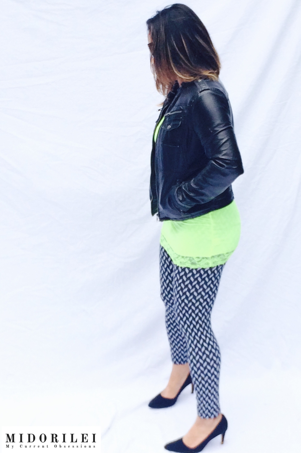 MidoriLei wears classic black pumps, modern graphic black and white leggings, a neon yellow top with lace, and a black motorcycle jacket