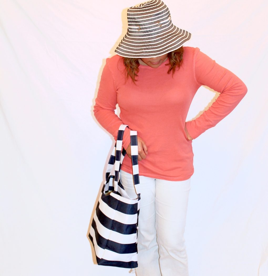 MidoriLei wears blue and white nautical striped tote and hat, coral top, white jeans, and white sandals