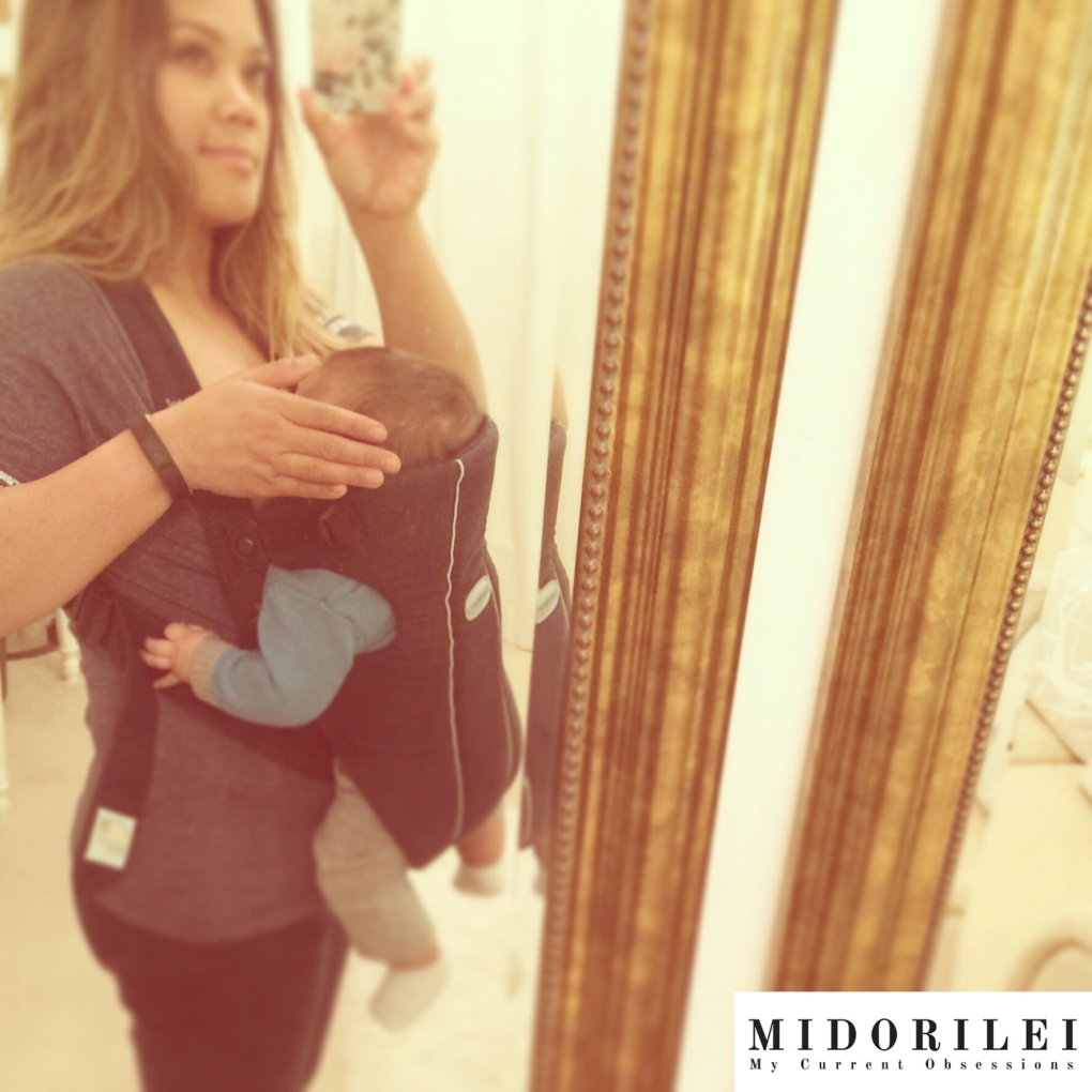 MidoriLei takes a selfie wearing a baby bjorn carrier and breastfeeding in front of a gold mirror with her baby Noah as a newborn