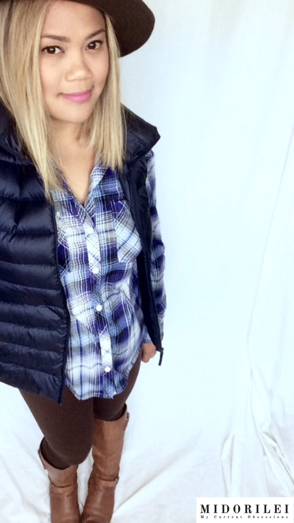MidoriLei wears a brown felt hat, uiniqlo navy puffer vest and stretchy blue and white plaid shirt with brown fleece lined leggings and brown naturalizer boots