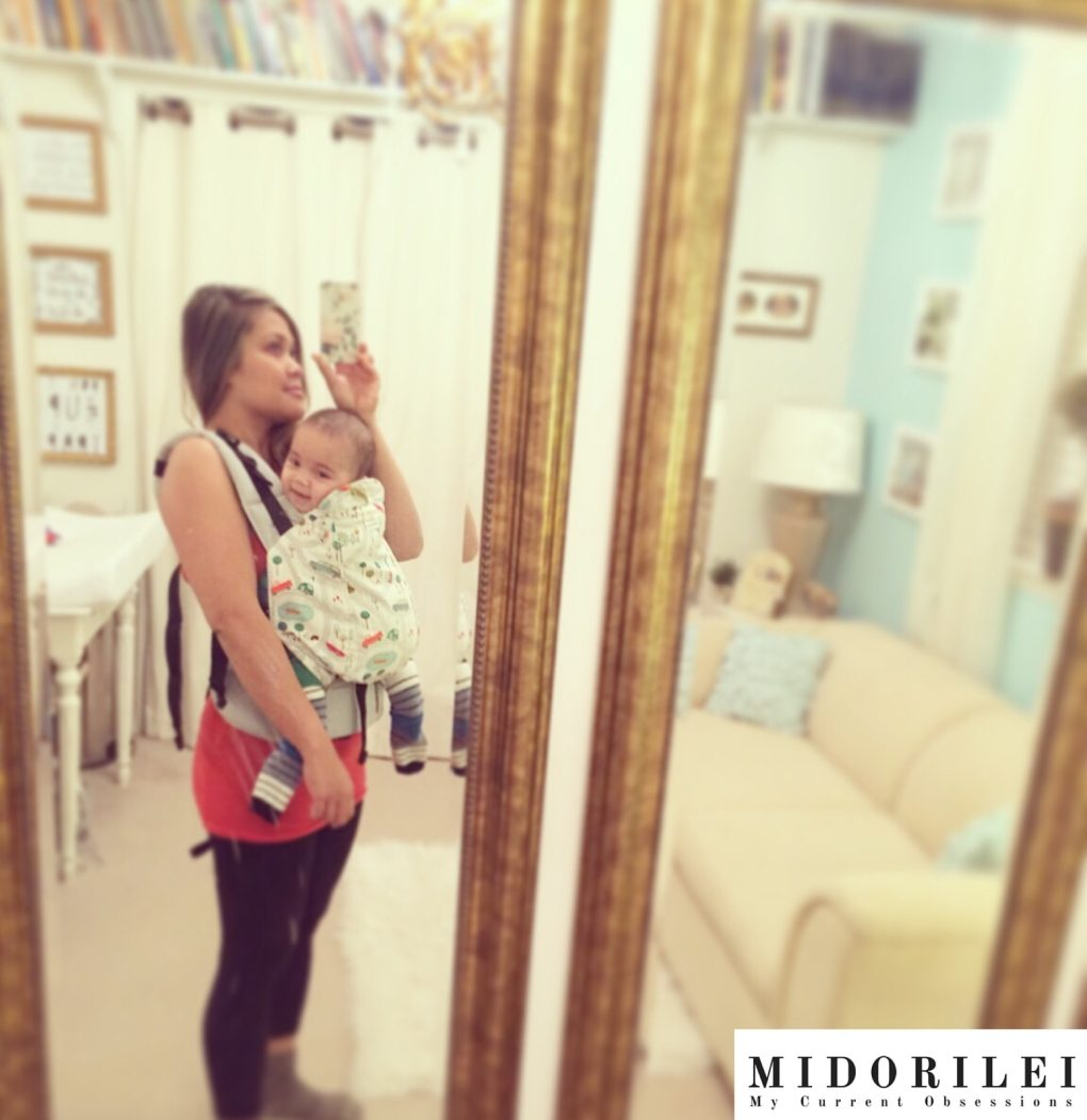 MidoriLei is babywearing Noah in a kinderpack and taking a selfie in her dressing room